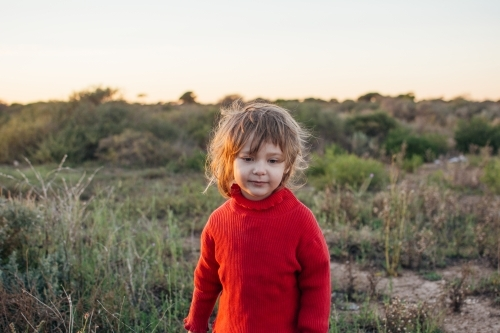 Young girl with messy hair standing in bushland