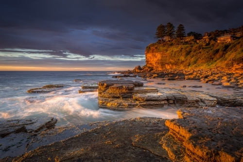 First light at Avalon beach, rich golden orange tones of light striking the cliff faces and rocks