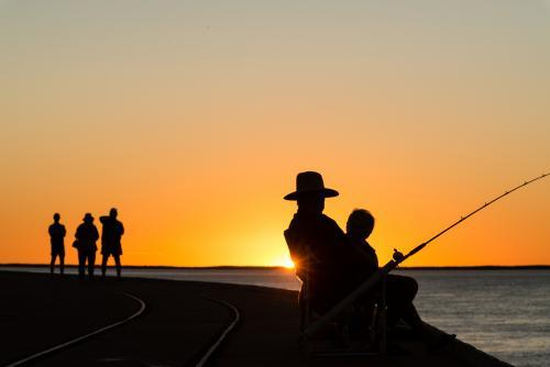 Fisherman and people silhouetted in sunset