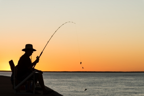 Fisherman silhouetted in the sunset