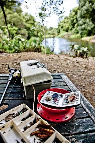 Fishing Tackle and box on Table with river in background