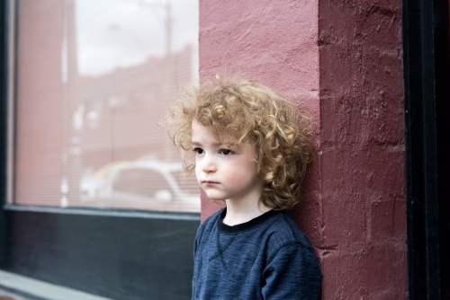 Young boy with curly hair standing against a pink brick wall