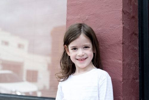 Young girl smiling, standing against a pink brick wall with a window reflecting the street