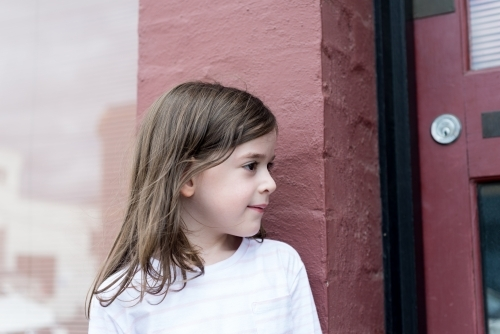 Profile of a young girl standing against a pink brick wall