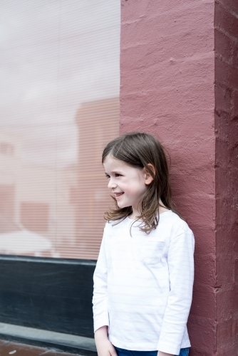 Young girl smiling, standing in front of a pink brick wall with a window reflecting the street