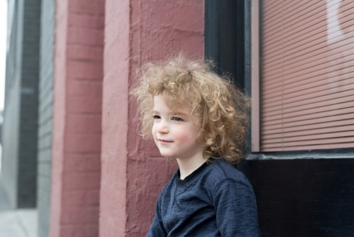 Young boy with curly hair outside a pink and green building