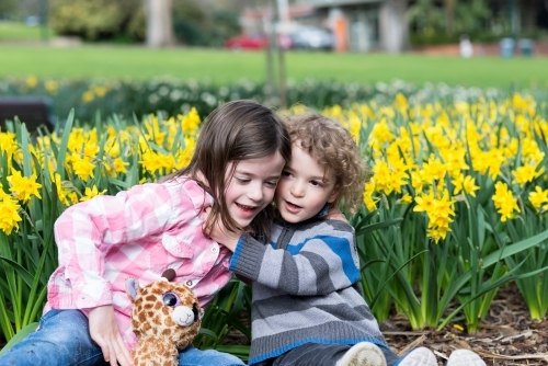 Young brother and sister playing in a daffodil garden