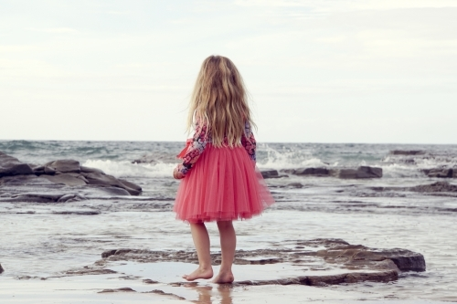 five year old walking along beach looking away