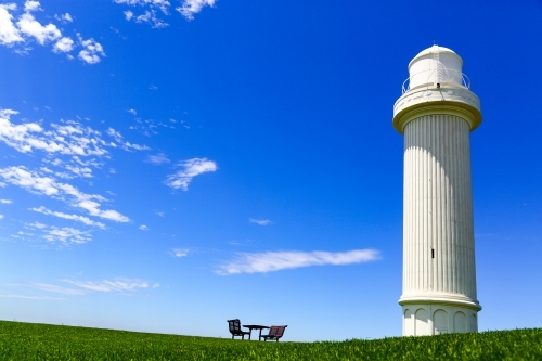 Flagstaff Hill Lighthouse, two benches and a table under a summer sky at Wollongong, NSW