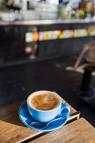 Flat white coffee on a wooden table