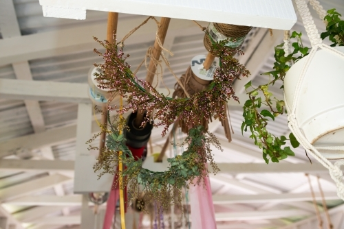 Floral flower crowns and ribbons hanging from the ceiling of a florist workshop