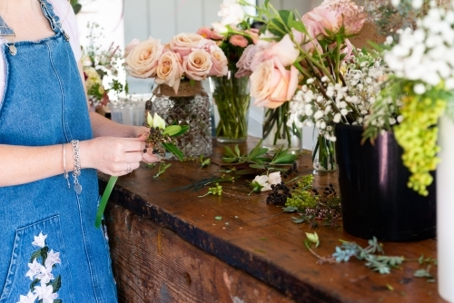Florist preparing wedding buttonholes and small corsages at a work bench full of flowers