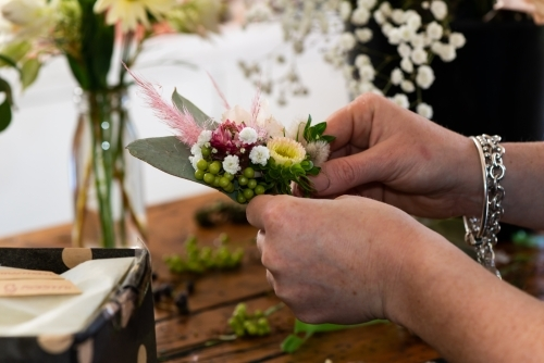 Florists hands holding a small pretty corsage for wedding,