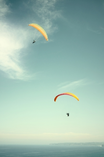 Pair of parachutes / parasailers on a clear day