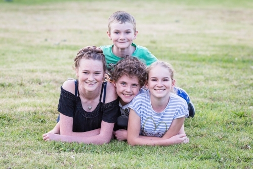 Four children family lying on grass together smiling