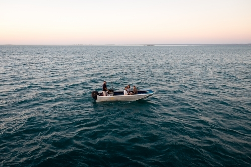 Four people sitting in a dinghy in remote ocean at sunset