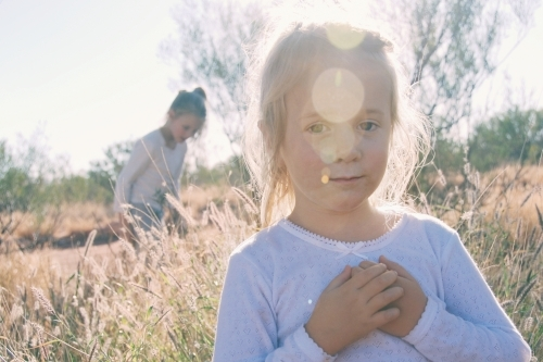 Four year old girl standing in a paddock with sun flare