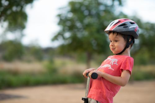 Cute mixed race boy wearing a helmet and riding his scooter