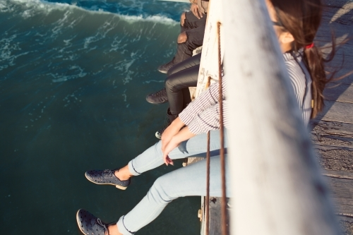 Friends dangling legs over a jetty