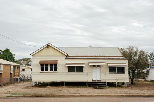 Front-on view of cream coloured Queenslander Home with brown trimming