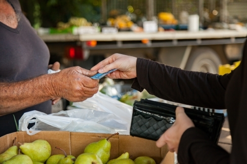 Woman handing cash over to Aussie farmer at produce stall