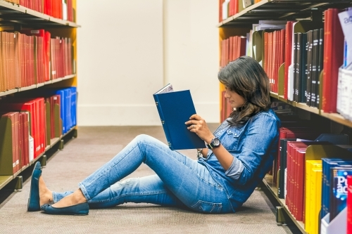 Full Length Of Woman Reading Book Amidst Shelves At Library