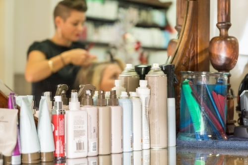 A row of hair care products in front of a mirror in a salon
