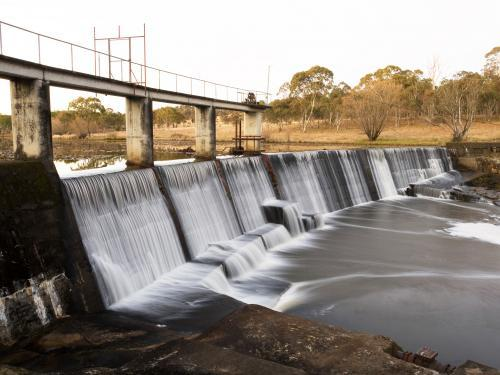 Water flowing over a curved concrete dam wall