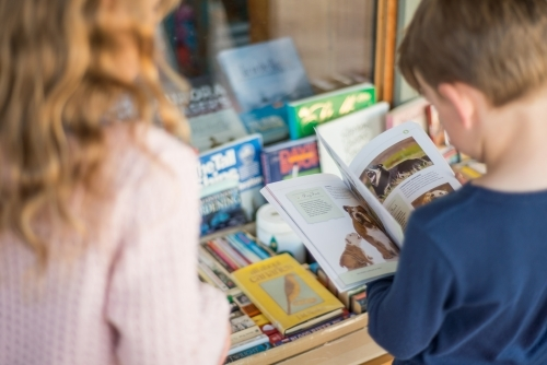 Girl and boy looking at books in front of a shop