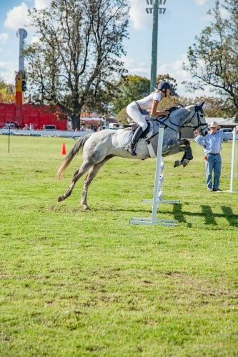 Girl and horse jumping a fence in a show jumping competition