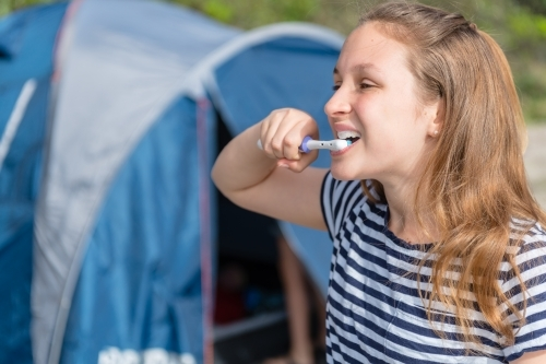 girl brushing her teeth on a camping trip