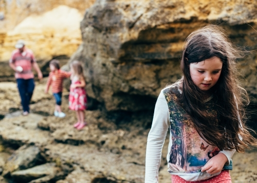 Girl carrying shells, family in background. Exploring limestone beach