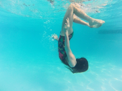 Girl doing somersaults underwater in a pool