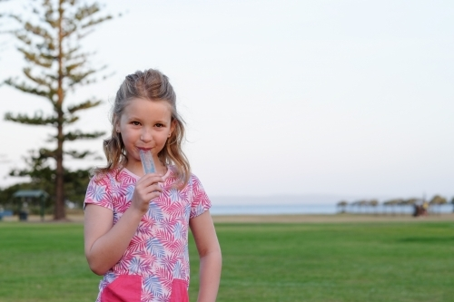 Girl eating an ice block in the park