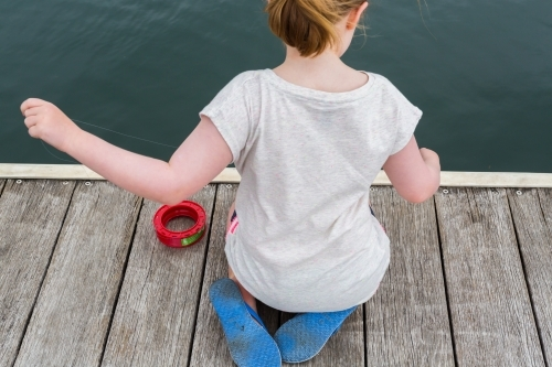 girl fishing with a hand reel from a wooden jetty