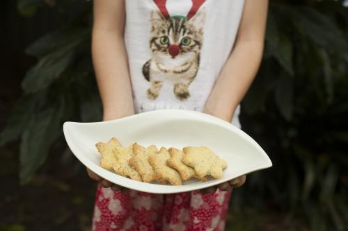 Girl holding a plate of Christmas biscuits