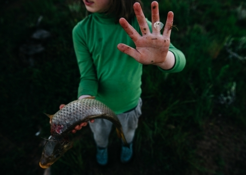 Girl holding carp showing dirty hand