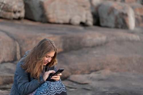 Girl huddled in jacket outdoors looking at smartphone