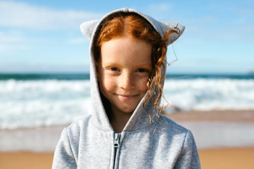 Girl in a hoodie with animal ears at the beach