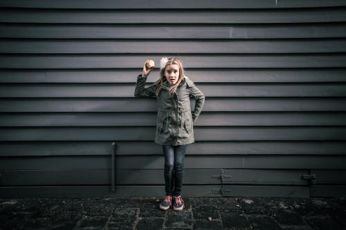 Girl in grey standing in front of grey weatherboards in the city holding an apple
