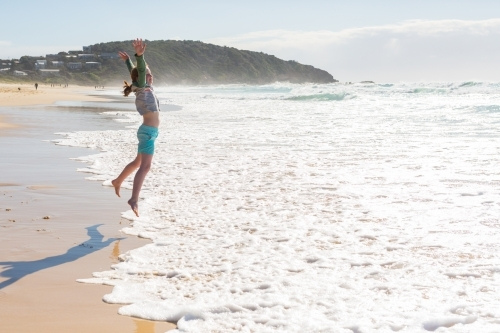 Girl jumping at a beach looking out to sea