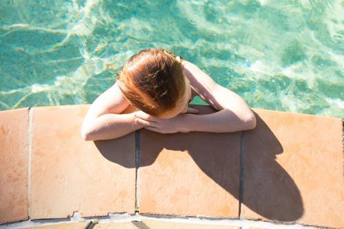 Girl leaning on the side of a swimming pool