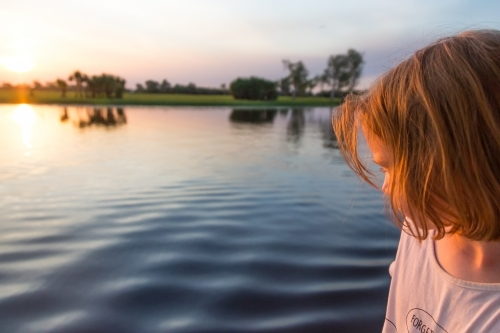 Girl looking at water on a boat cruise on yellow waters at sunset