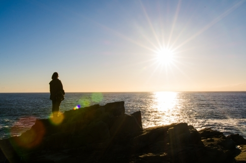 Girl looking out to sea during sunrise from a cliffside