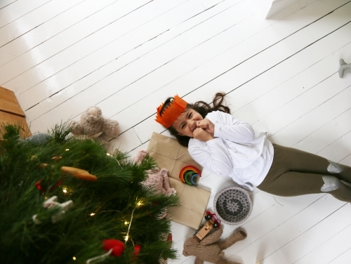 Girl lying on white floor looking up with Christmas tree and presents