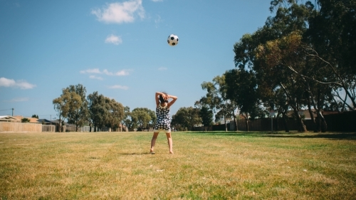 Girl playing soccer in the park with the ball in the air