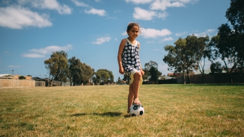 Girl playing soccer on the grass