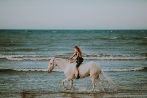 Girl riding horse in ocean waves