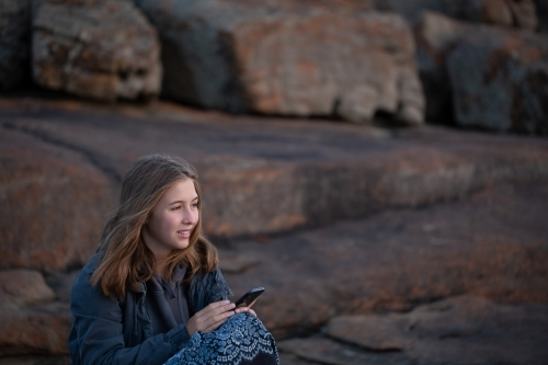Girl sitting alone outdoors with iPhone