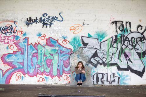 Girl sitting with graffiti on wall